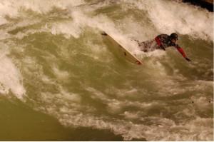 Eisbach-Surfer in München auf einer sogenannten stehenden Welle am Haus der Kunst